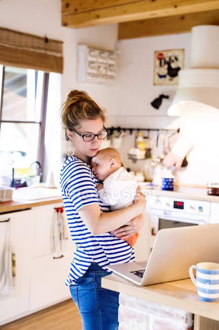 Мать с ребенком на кухне смотрит на ноутбук — стоковое фото