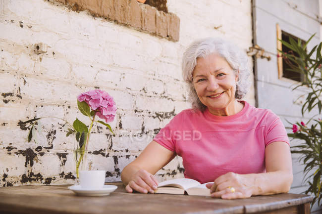Senior woman sitting in courtyard, drinking coffee — Stock Photo