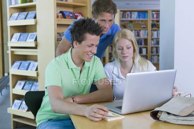 Étudiants souriants avec ordinateur portable dans une bibliothèque d'apprentissage — Photo de stock