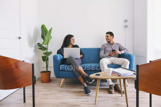 Jeunes gens d'affaires travaillant détendus sur le canapé — Photo de stock