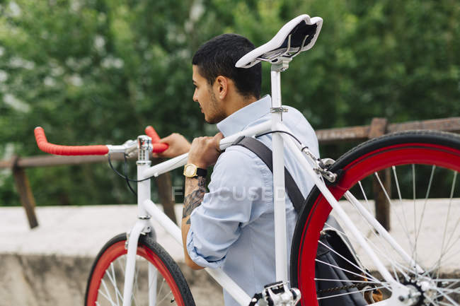 Young man carrying a bicycle — Stock Photo