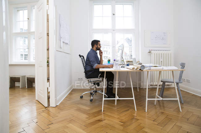 Creative professional working on computer in modern office — Stock Photo