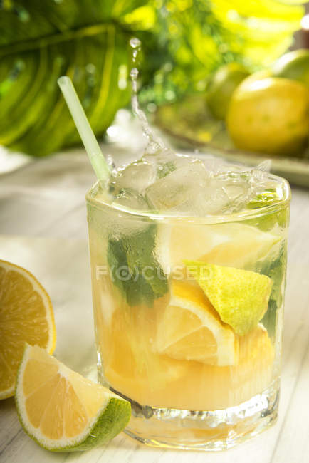 Glass of homemade lemonade with splash and ingredients — Stock Photo
