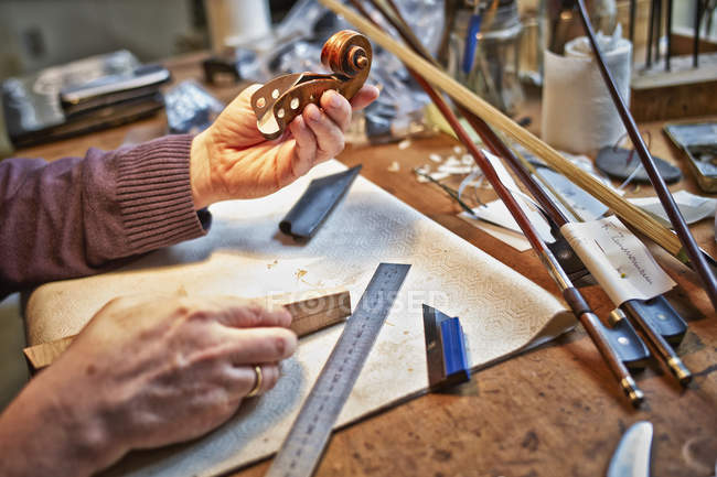 Close-up of Violin maker holding scroll in workshop — Stock Photo
