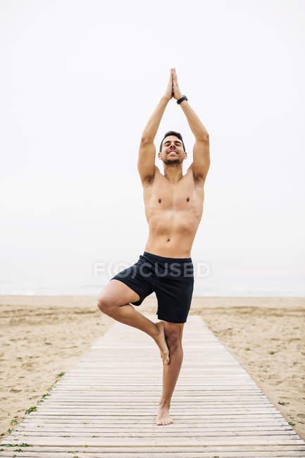 Joven practicando yoga en el paseo marítimo en la playa - foto de stock
