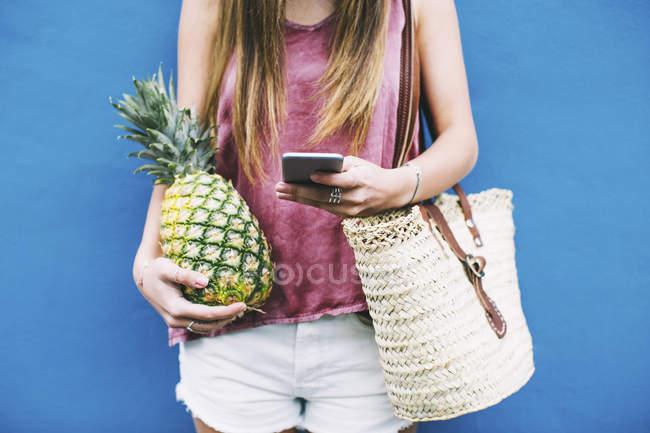 Frau mit Strandtasche, Handy und Ananas auf blauem Hintergrund — Stockfoto