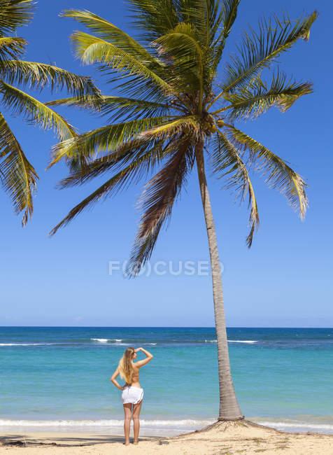 Доминиканская Республика, молодая женщина, глядя через тропический пляж — стоковое фото