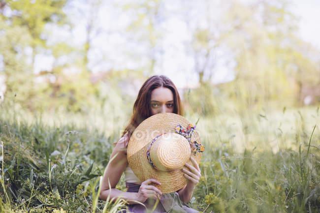 Молодая женщина приседает на лугу весной — стоковое фото