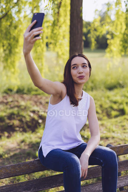 Woman taking a selfie while sitting a bench at the park — Stock Photo
