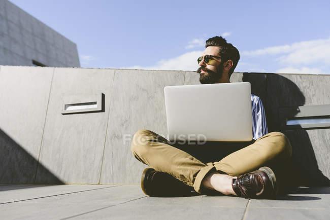 Hombre sentado en tierra con ordenador portátil - foto de stock