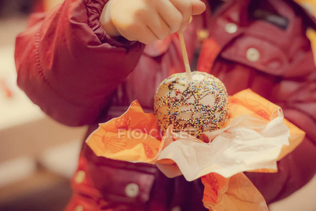 Garçon tenant des bonbons pomme, gros plan — Photo de stock