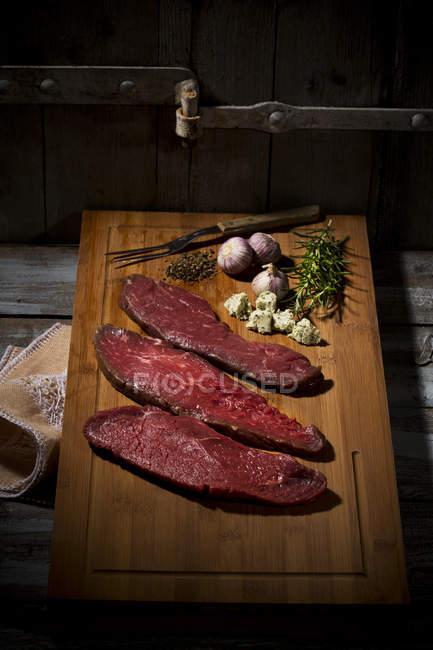 Бифштекс, чеснок, розмарин, масло с пряностями и перец на разделочная доска — стоковое фото