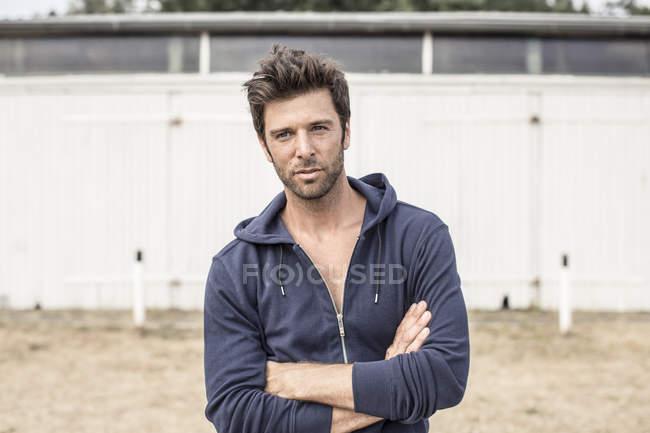 Ritratto di uomo con giacca con cappuccio in piedi con le braccia incrociate — Foto stock