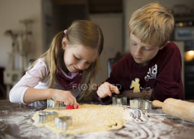 Boy and girl cutting out cookies with cookie cutter — Stock Photo