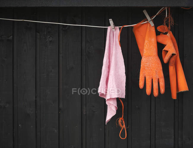 Clothesline with rubber gloves and dishrag — Stock Photo