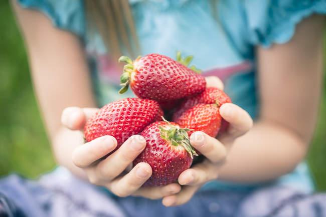 Ragazzina con in mano una manciata di fragole fresche — Foto stock