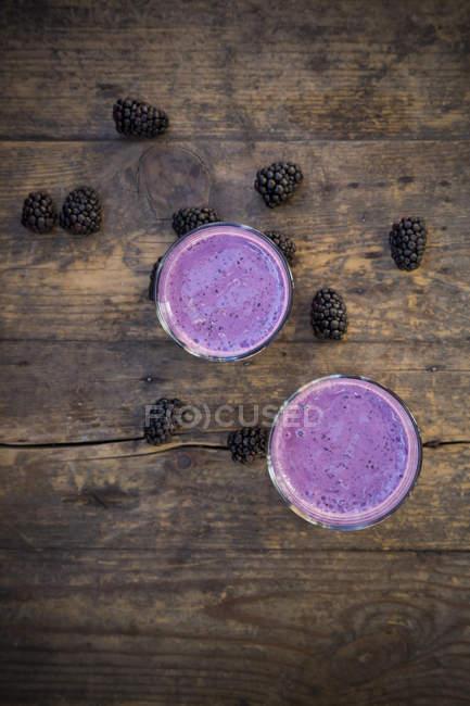 Vue de dessus de deux verres de smoothie de blackberry et BlackBerry sur table en bois — Photo de stock