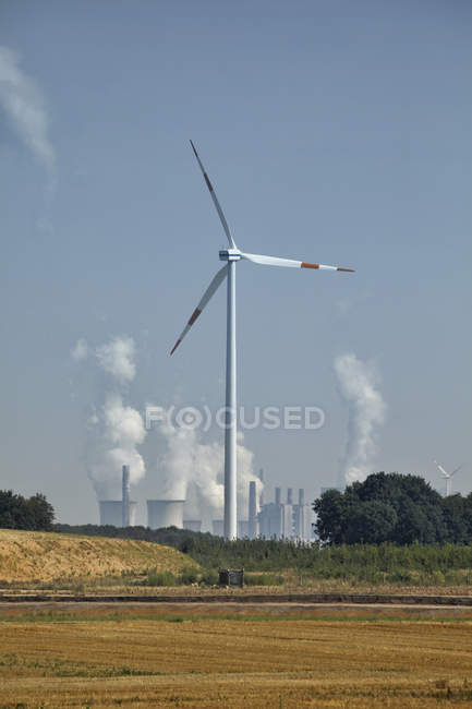 Germany, North Rhine-Westphalia, Wind turbine in front of brown coal power station — Stock Photo