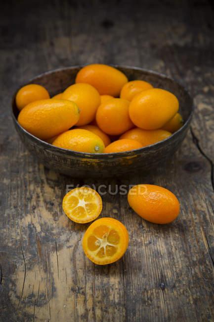 Schüssel mit frischen Kumquats und halbierte Kumquat auf dunklem Holz — Stockfoto