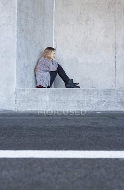 Portrait d'adolescente malheureuse, assis sur le mur en béton — Photo de stock