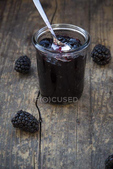 Close-up de preservar o pote de geleia de blackberry com colher e amoras na mesa de madeira — Fotografia de Stock