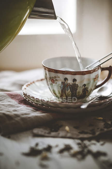 Pouring hot water in a cup with Chinese green jasmin tea — Stock Photo