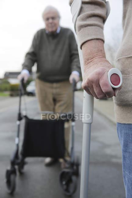 Casal sênior com andador de rodas e muleta — Fotografia de Stock