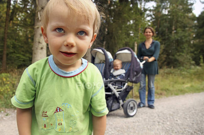 Portrait of little boy on the move with mother and brother on background — Stock Photo