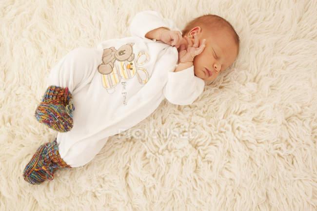 Bonito recém-nascido dormir na pele de carneiro — Fotografia de Stock