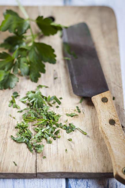 Prezzemolo tritato su tagliere di legno con coltello — Foto stock