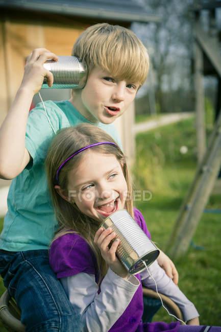 Мальчик и девочка играют с жестяным телефоном — стоковое фото