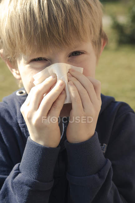 Portrait of boy blowing his nose with tissue handkerchief — Stock Photo