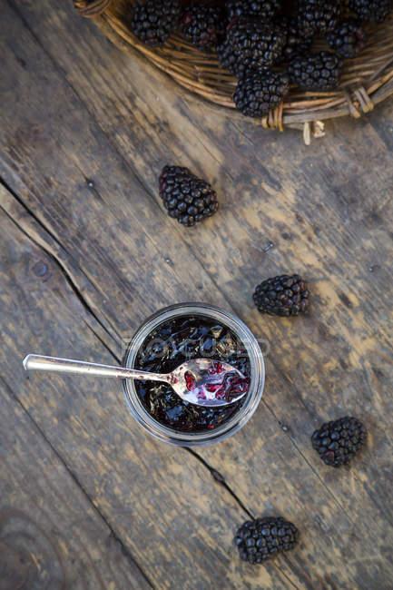 Vista superior da cesta de amoras e preservando pote de geleia de blackberry com colher de madeira mesa — Fotografia de Stock