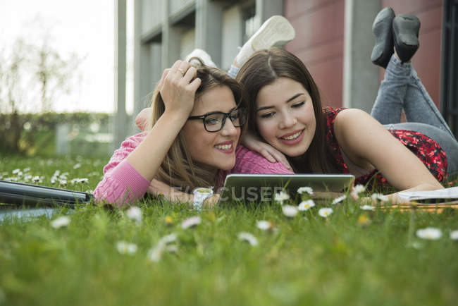 Zwei junge Frauen nutzen digitales Tablet auf Wiese — Stockfoto
