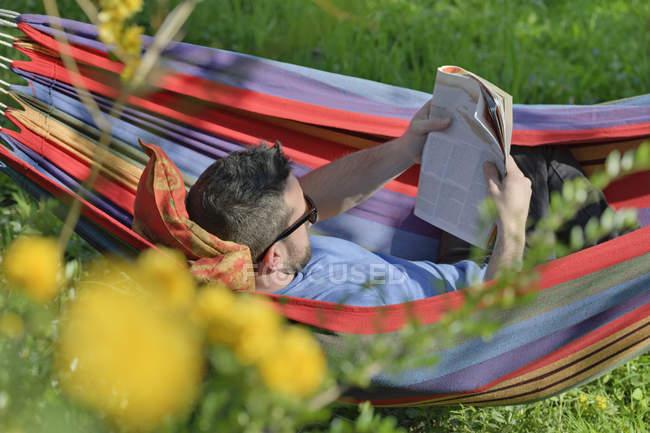 Молодой человек, лежа в гамаке и чтения журнала — стоковое фото