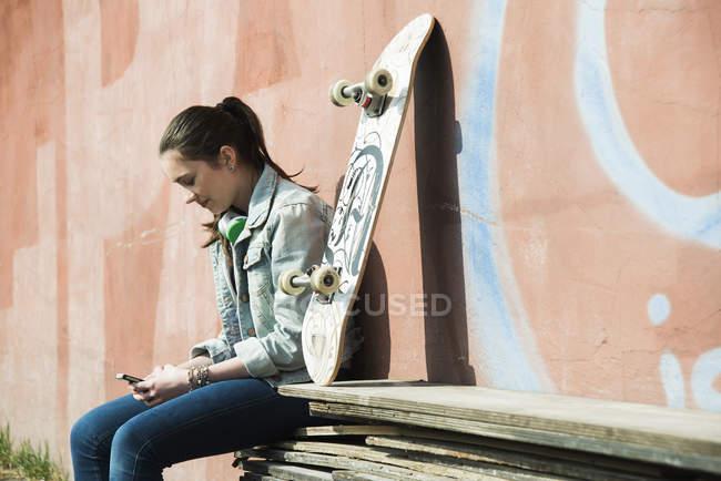 Adolescente avec planche à roulettes à l'aide de smartphone — Photo de stock