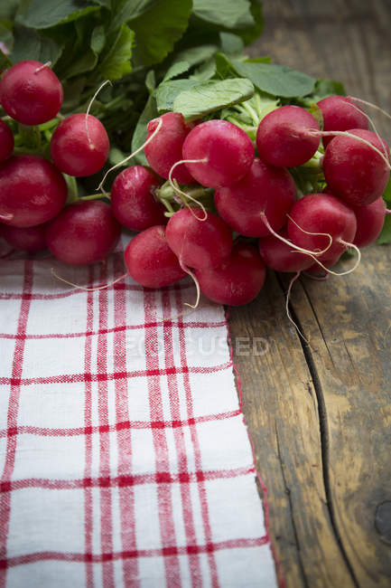 Bunches of red radishes on kitchen towel on wooden table — Stock Photo