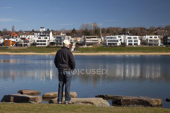 Германия, Северный Рейн-Вестфалия, Дортмунд-Hoerde, озеро Phoenix, старший стоял на берегу озера и глядя на вид — стоковое фото