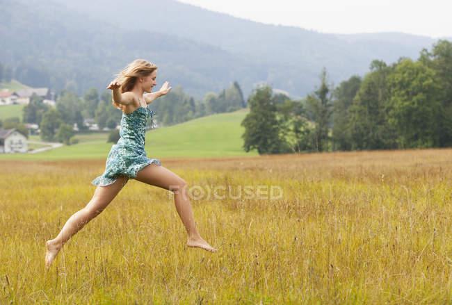 Austria, Salzkammergut, Mondsee, jovem saltando em um prado — Fotografia de Stock