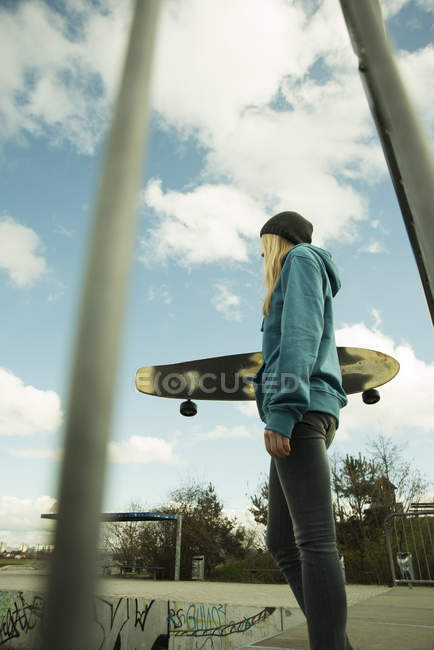 Young woman at skate park with longboard — Stock Photo