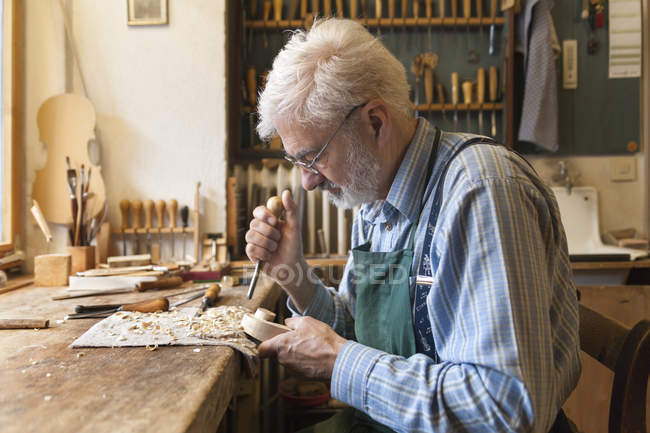 Closeup view of senior caucasian violin maker at work in workshop — Stock Photo