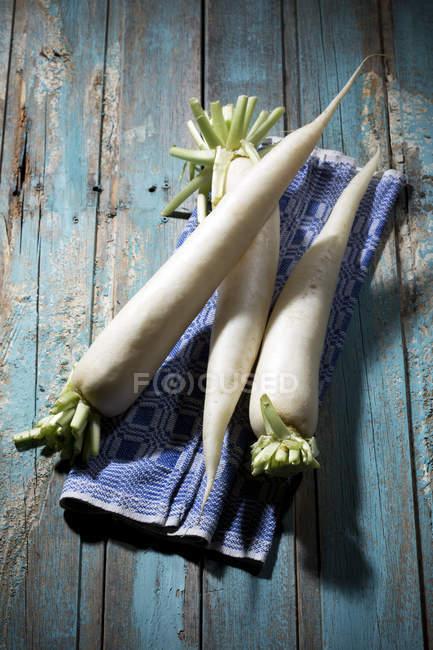 White radishes on shabby blue wooden surface with napkin — Stock Photo
