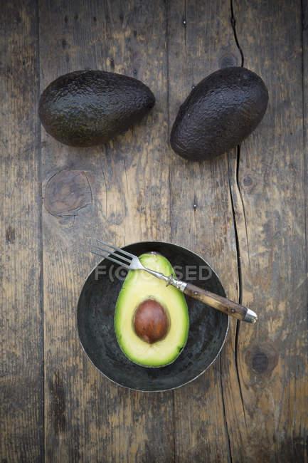 Ganze und halbierte Avocados auf dunklem Holz mit Teller und Gabel — Stockfoto