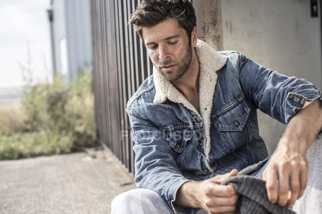 Thoughtful man wearing denim jacket sitting in front of building — Stock Photo