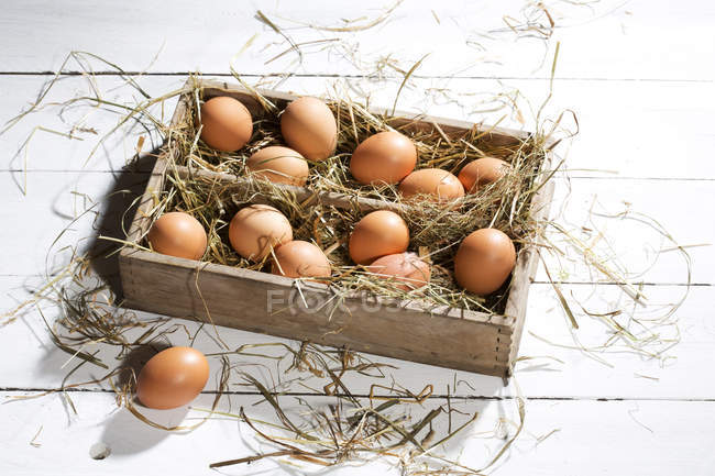 Top view of wooden box of brown eggs and hay on white wooden table — Stock Photo