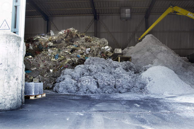 Piles of different materials in industrial hall at recycling yard — Stock Photo