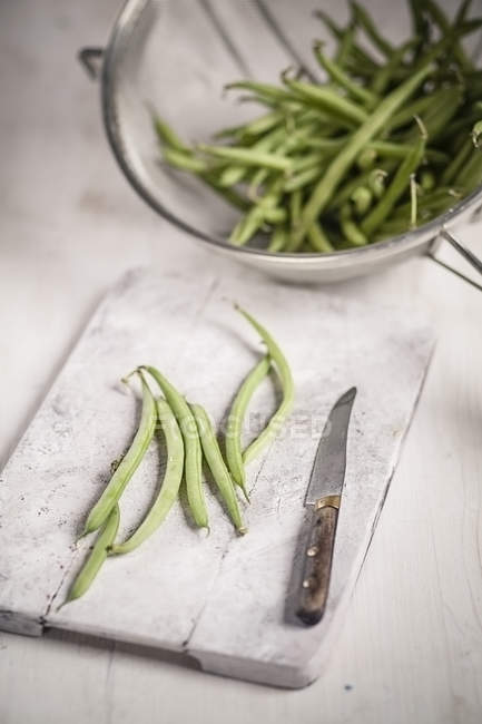 Green beans in strainer and on white wooden chopping board — Stock Photo