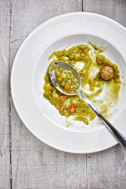 Piatto di zuppa con avanzi di stufato di piselli su legno grigio, vista elevata — Foto stock