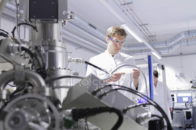 Scientist standing in analytical laboratory with scanning electron microscope in foreground — Stock Photo