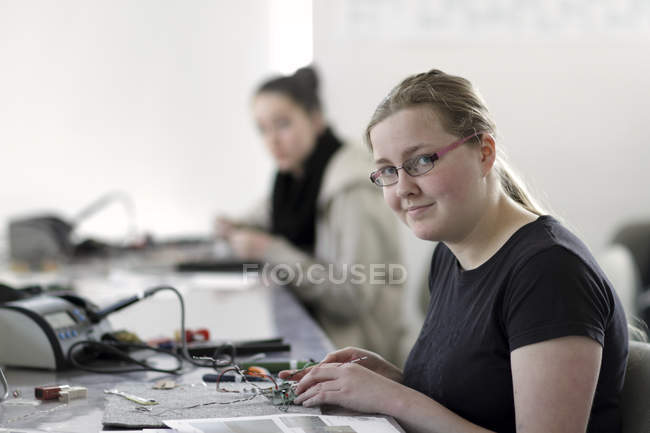 Two young women working on optical sensor in an electronic workshop — Stock Photo